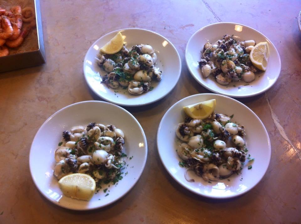 quattro piatti di pesce con limone