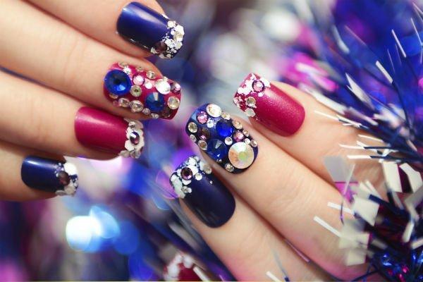unghie viola e fucsia con applicazioni di perline e brilli