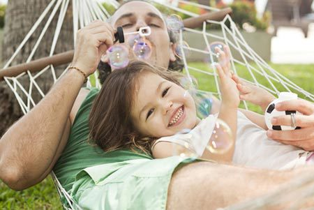 Smiling young girl on hammock with father in Cincinnati