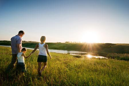 A family walking in field at sunset
