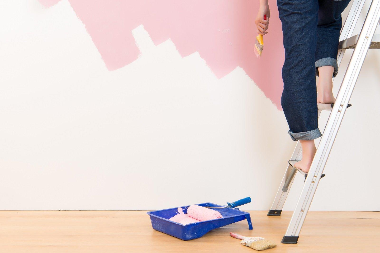 donna che dipinge un muro di rosa