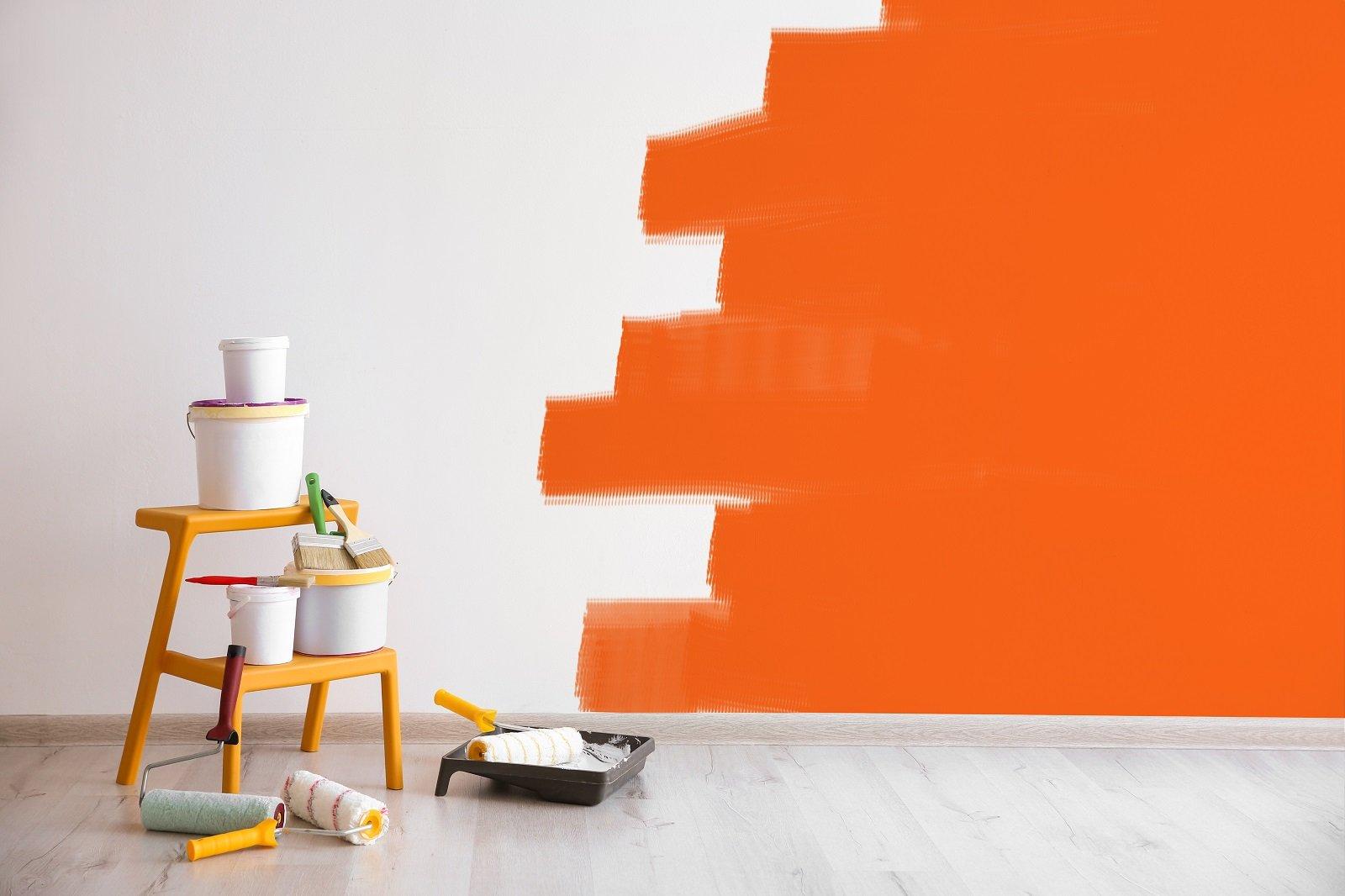 barattoli di vernice davanti a un muro arancione