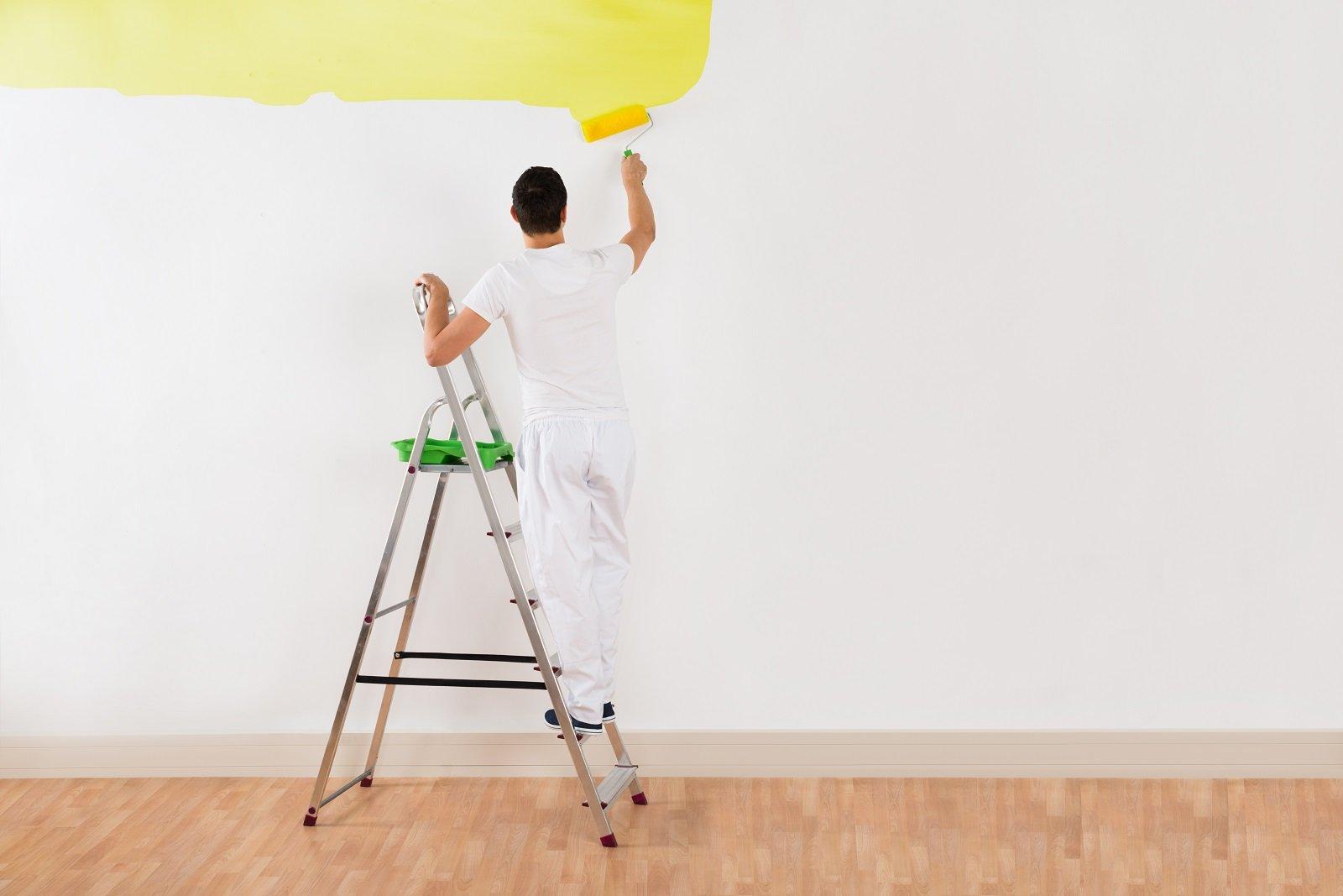 uomo che dipinge un muro di giallo