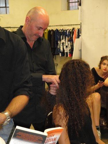 mani di parrucchiere con capelli di una modella in salone