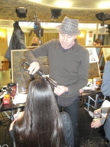 parrucchiere con cappello fa i boccoli a una modella con la piastra