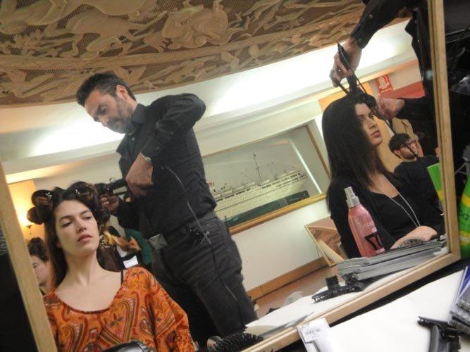 parrucchiere usano piastre per fare i boccoli a delle modelle