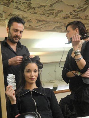 modella mentre guarda la macchina fotografica dallo specchio e passa delle mollette al parrucchiere
