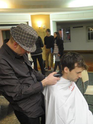 parrucchiere mentre usa un rasoio per tagliare i capelli a un modello