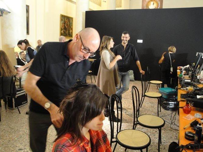 parrucchiere fa i boccoli a una modella in un salone