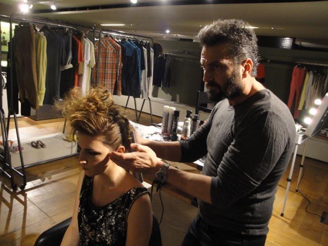 un parrucchiere con una modella durante lavoro in salone con vestiti per modelle