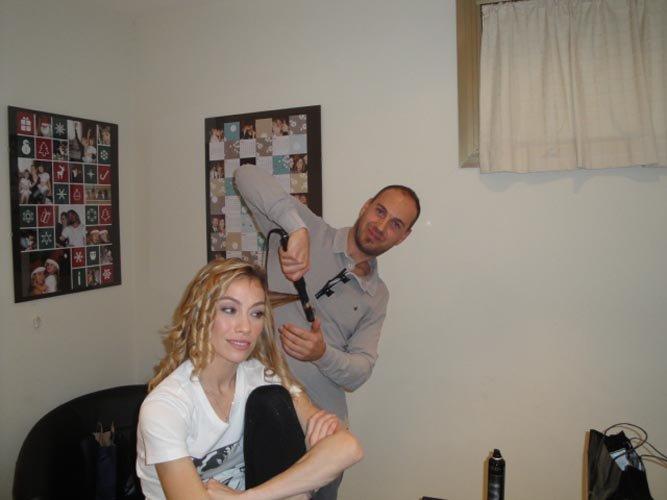 vista angolare di salone con mani del parrucchiere che tagliano capelli  di una modella