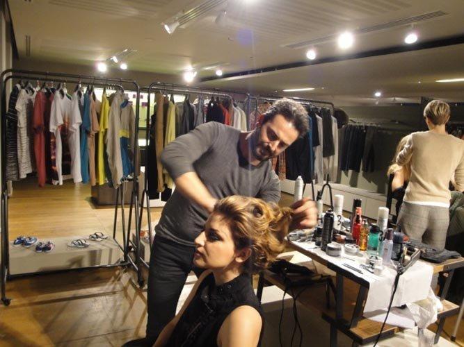 vista di una sala con vestiti appesi per modelle e un parrucchiere al lavoro con una modella