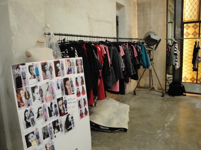 vista laterale di camerino con vestiti appesi e catalogo