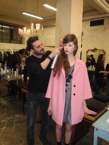parrucchiere durante finale tocca su capelli di una modella che vestito rosa