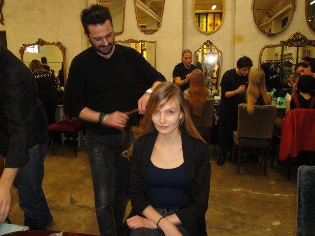 parrucchiere che tagliano capelli in salone di una modella