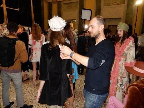 Parrucchiere mentre sistema capelli di una modella in un salone con altri modelle