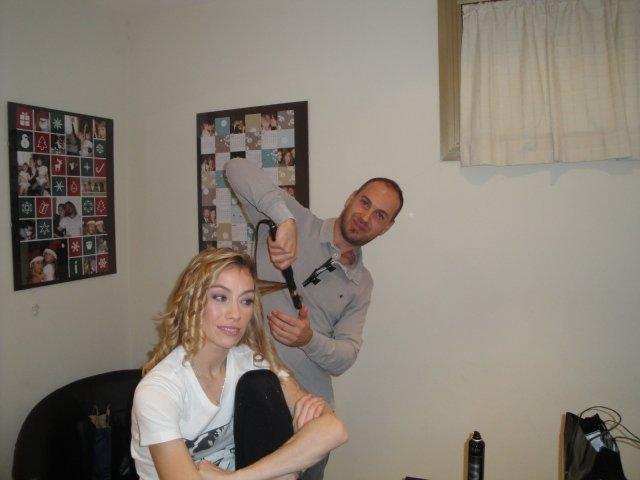 vista angolare di salone con mani del parrucchiere che tagliano capelli