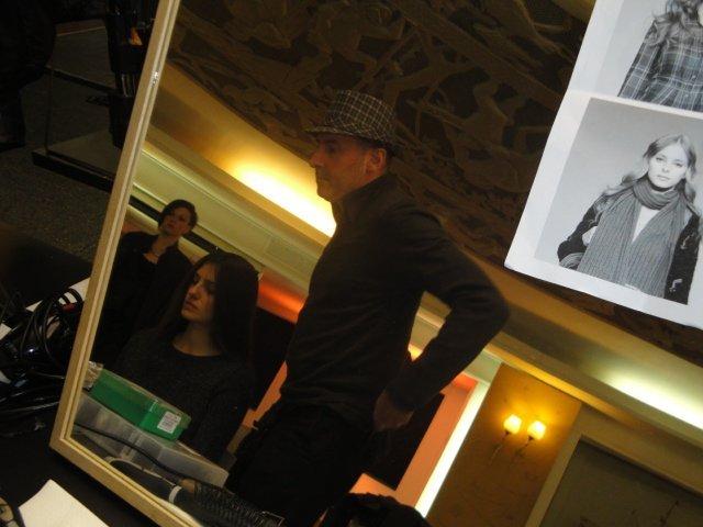 uomo con cappello si alza da una sedia in un camerino