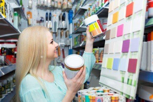 ragazza bionda sceglie barattoli di vernice