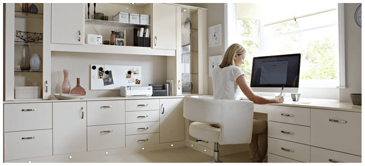 An office furnished with white, a lady is sat at a desk working.