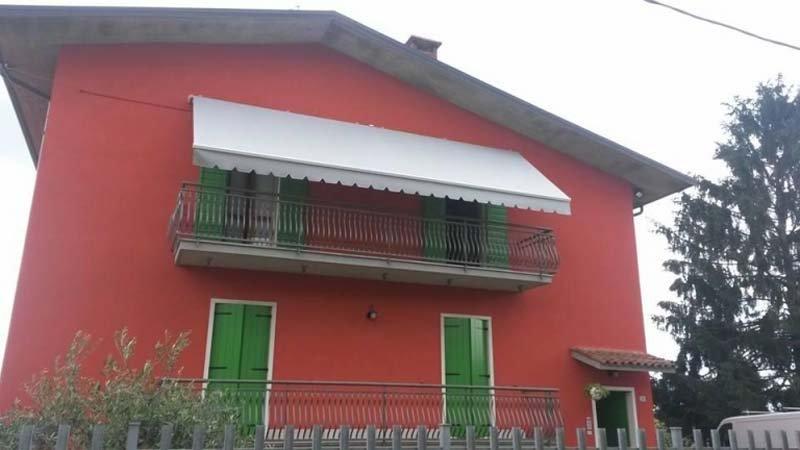 condominio rosso con terrazzo e tenda parasole