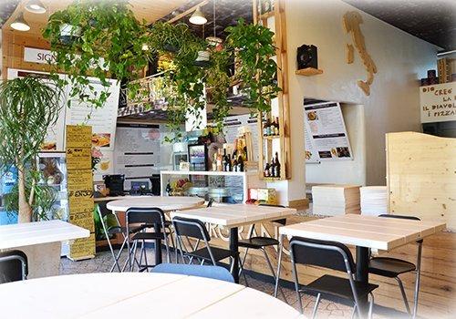 La terrazza della pizzeria piena di piante, nella parete una mappa dell'Italia fatto in legno