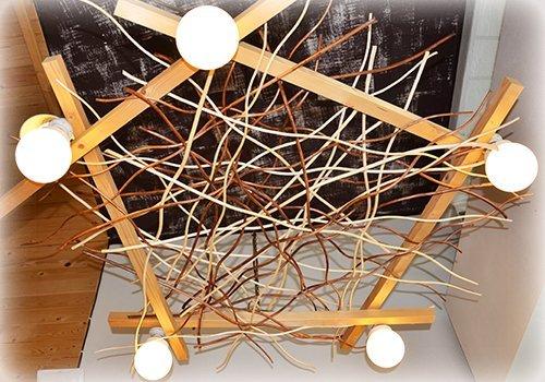 Lampada a tetto imitando un nido con legni  incrociati