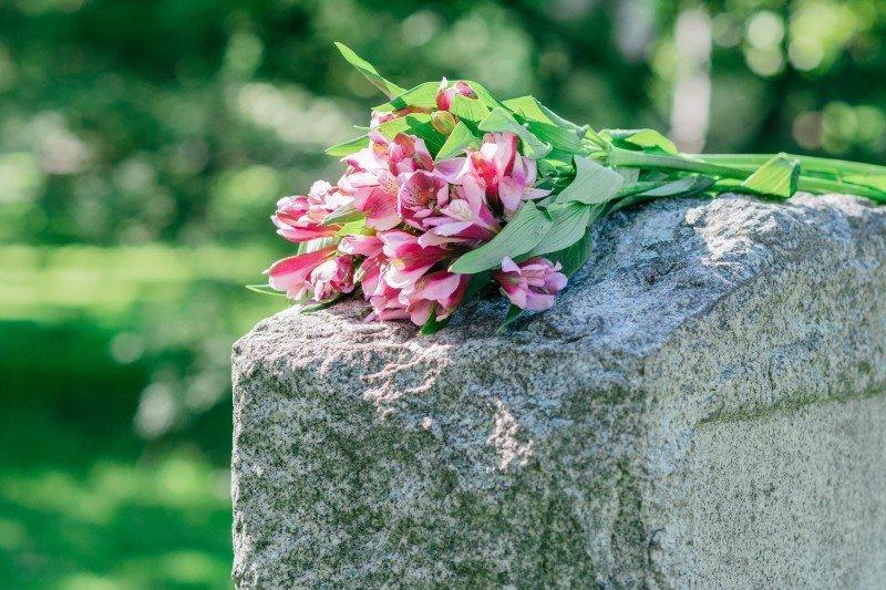 dei fiori viola su una lapide in pietra