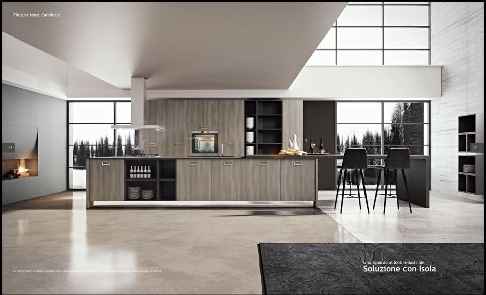 una cucina ampia in legno chiaro e due sgabelli neri