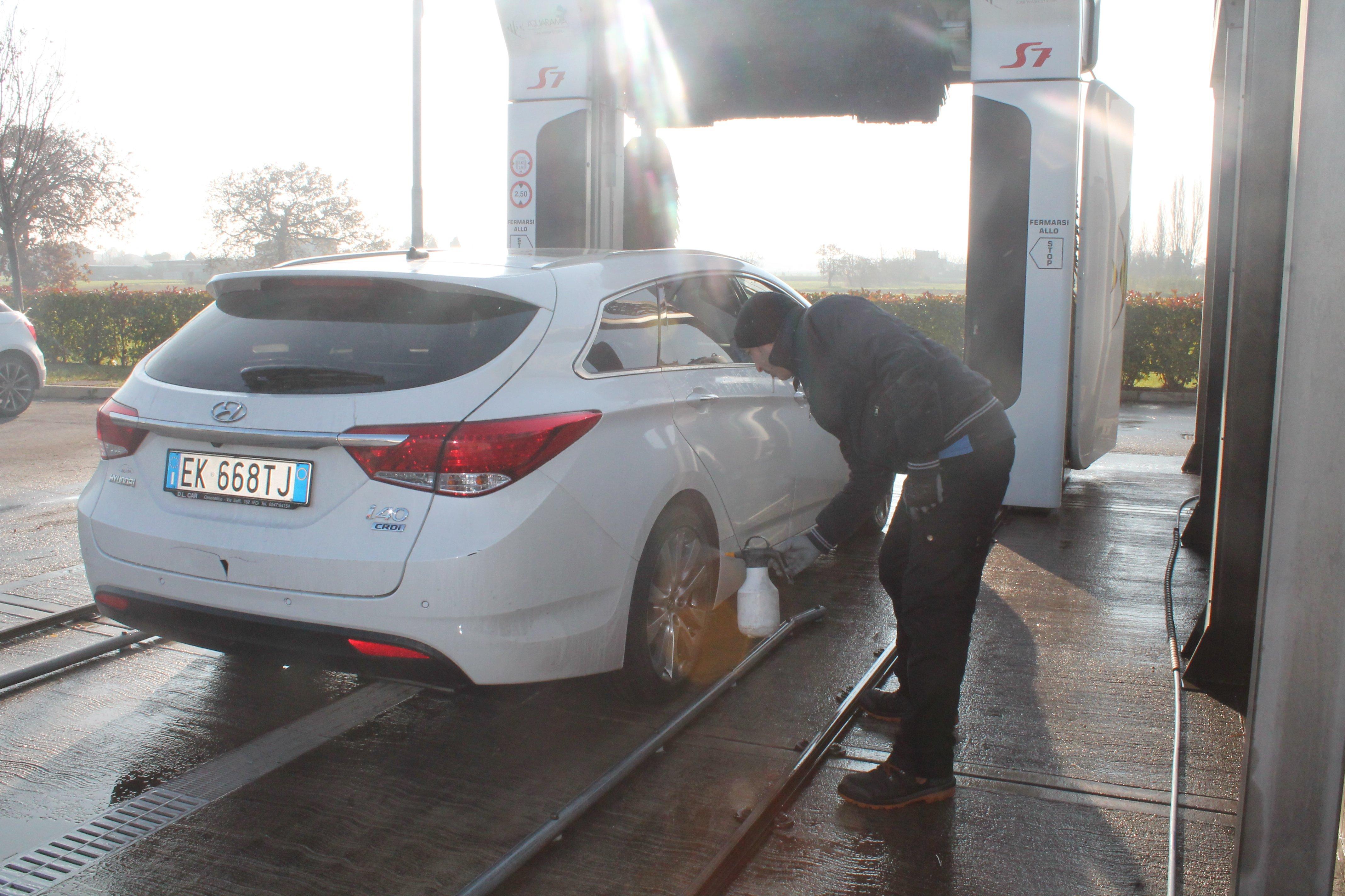 Addetto che lava una macchina bianca