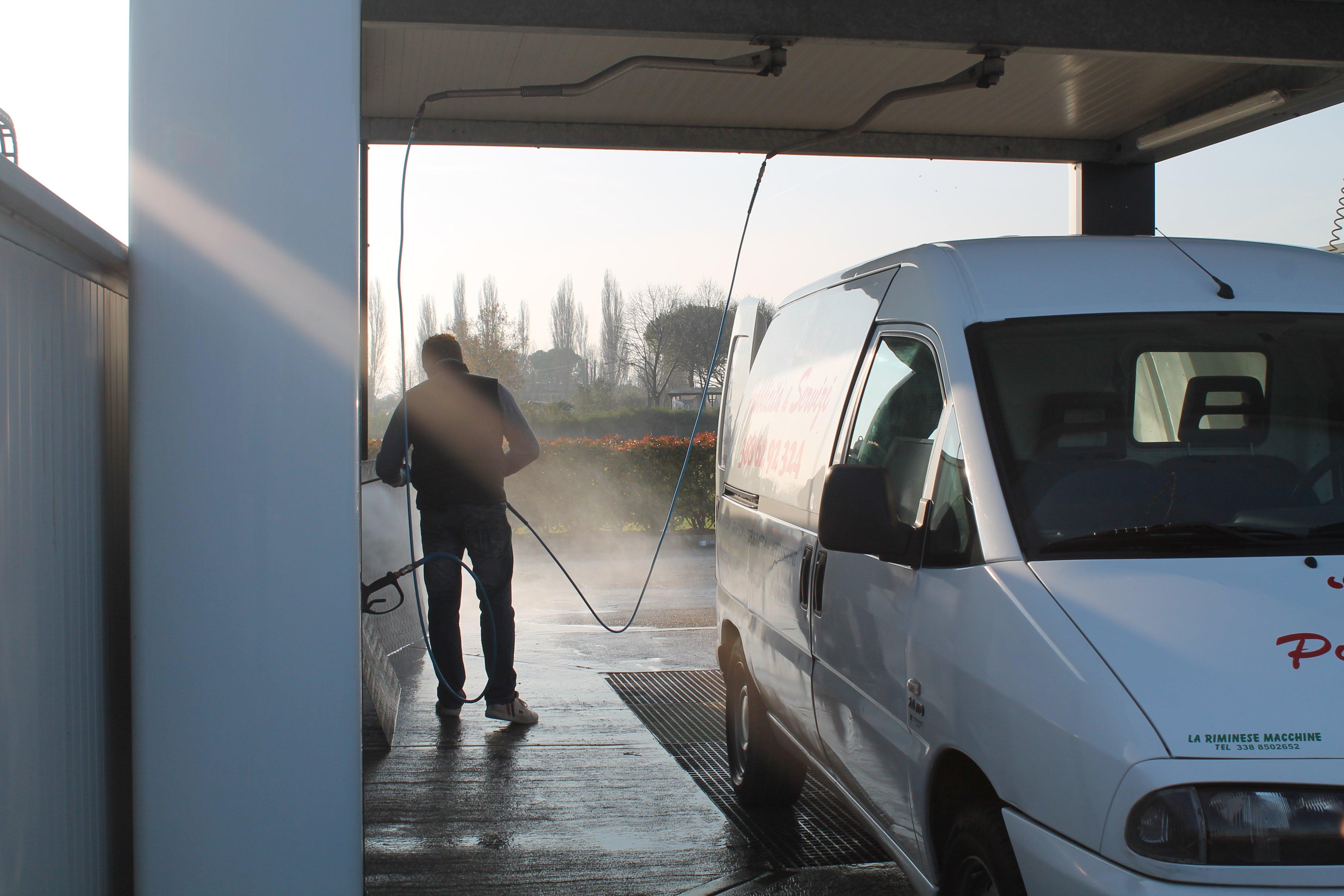 Un furgoncino bianco e una persona che lo lava