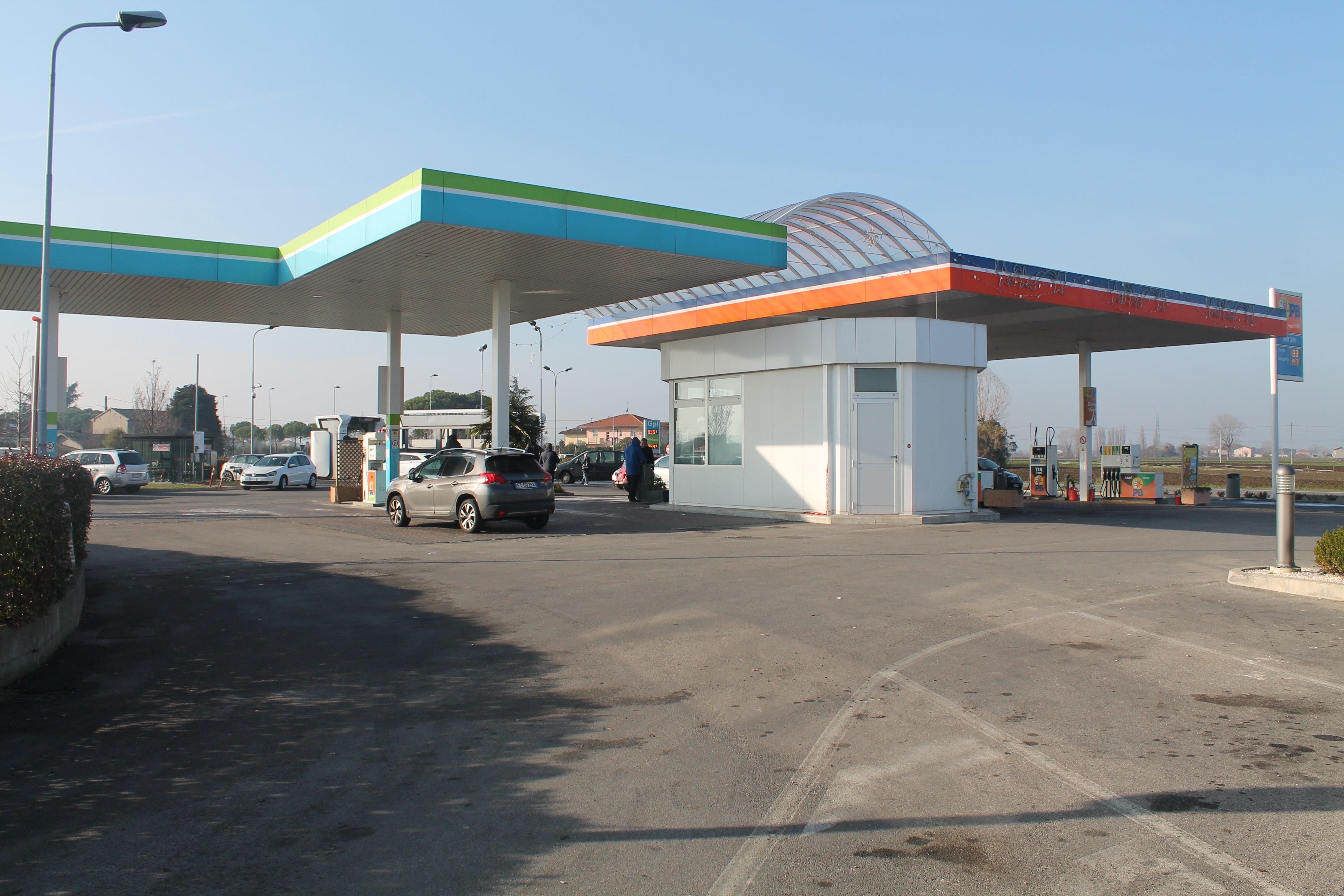 stazione di servizio con area parcheggio e una macchina grigia parcheggiata