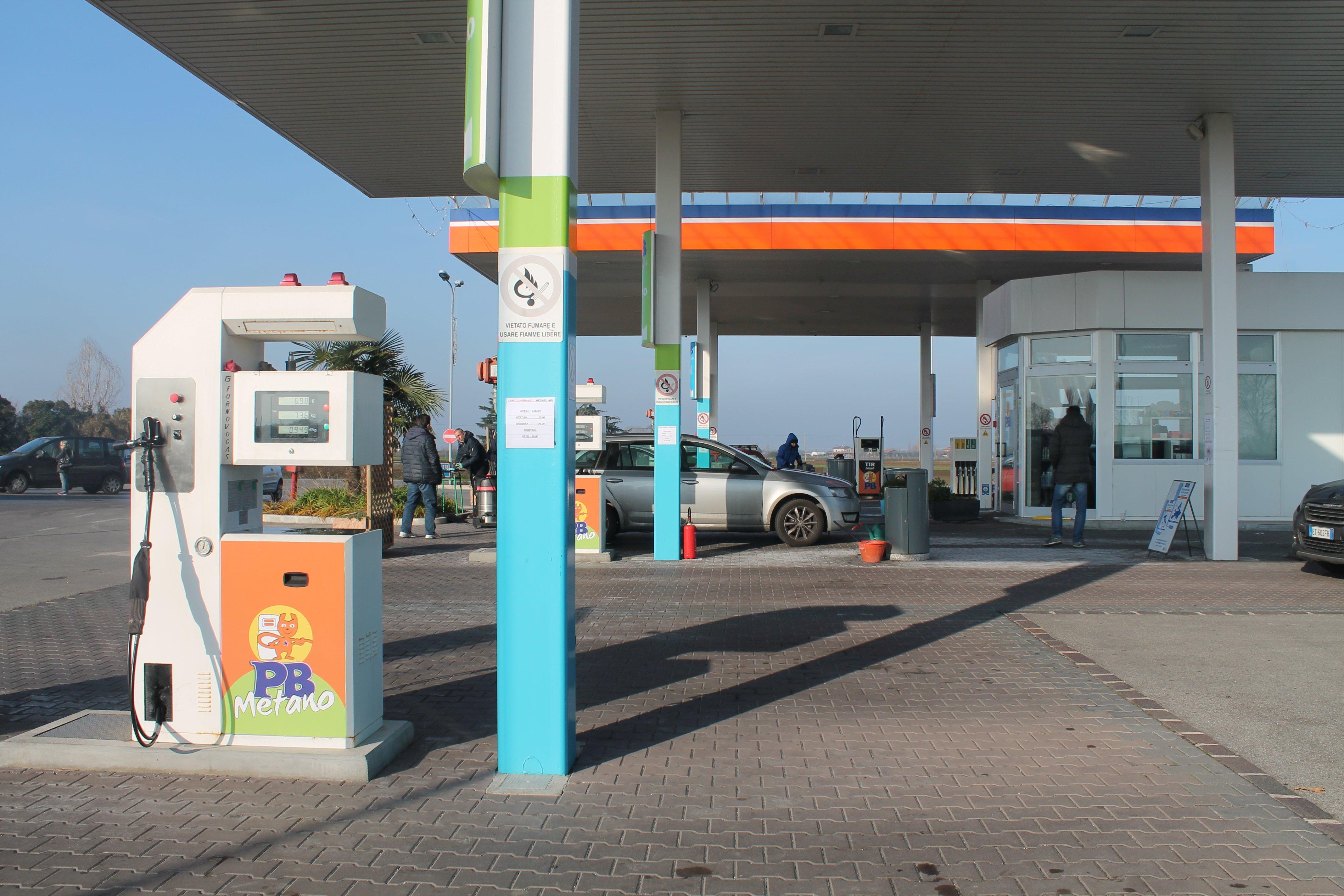 benzinaio con una macchina grigia parcheggiata