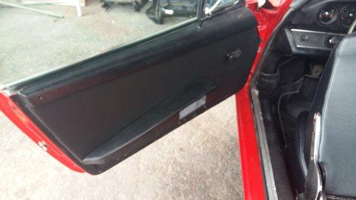 portiera di un auto rossa aperta con interni neri