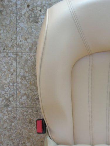 porzione di sedile bianco appoggiato sul pavimento con cintura di sicurezza