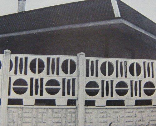 una ringhiera in cemento bianco e dietro una casa