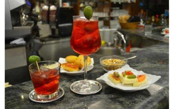 un tavolo apparecchiato per aperitivo con un drink e degli snack