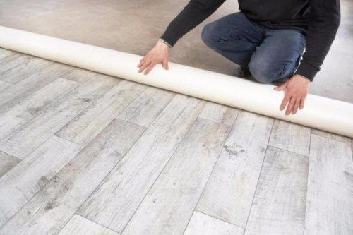 due mani di un uomo mentre appoggiano un tappeto sul pavimento