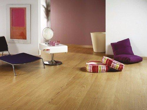 una sala con un pavimento in legno chiaro e dei cuscini sul pavimento