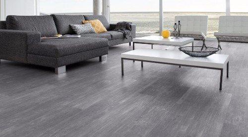 una sala con dei divani grigi e un pavimento in legno di color grigio