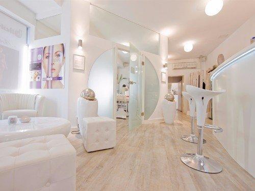 interno di un parrucchiere con dei divani , pouf bianco e un pavimento in legno