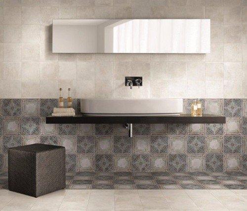 un bagno con delle piastrelle di color grigio, avorio e una mensola con un lavabo