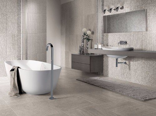 un bagno con una vasca, un lavabo e delle piastrelle di color grigio