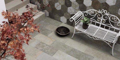 una panchina in ferro di color bianco e un muro con delle piastrelle a forma ottagonale