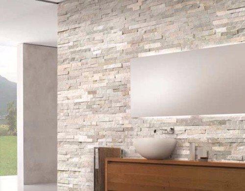 un bagno con un lavabo rotondo e un muro con le piastrelle a effetto pietra