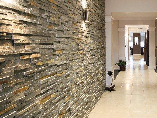 un corridoio lungo con pavimento in piastrelle di color avorio e un muro con le piastrelle a effetto pietra