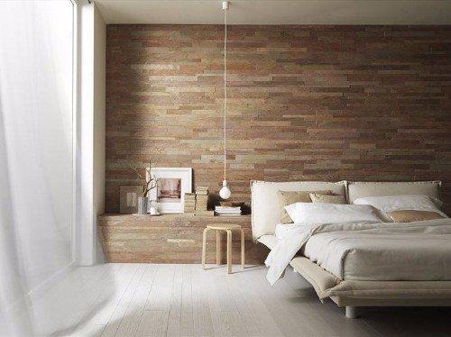 una camera con un letto e il  muro dietro con piastrelle a sfumature marroni