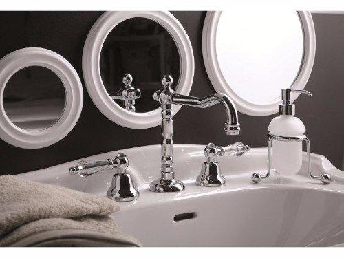 un lavabo con un rubinetto in acciaio inox e tre specchi rotondi al muro