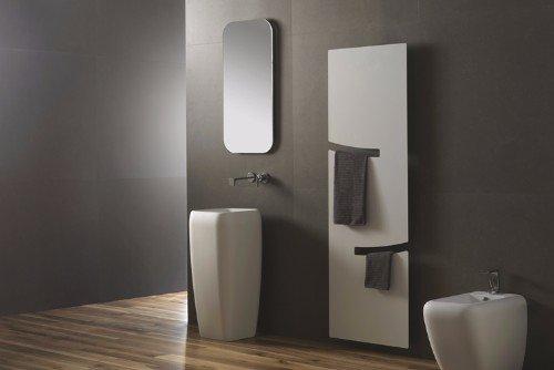 un bagno con un lavabo alto e uno specchio al muro