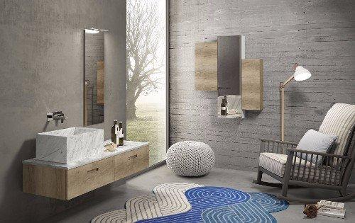 un bagno con un lavabo in marmo, uno specchio a muro e davanti una poltrona a dondolo
